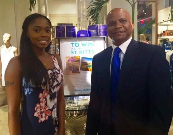 The Hon. Lindsay F.P. Grant, Minister of Tourism, International Trade, Industry and Commerce at the Tommy Bahama flagship store in New York City with a Tommy Bahama employee, in front of the 'Escape to St. Kitts' Sweepstakes in-store signage.