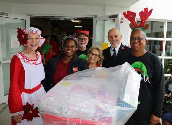 Pam Masters, Jeff Zelkowitz, Pilar Garcia, Major Stephen Long and Betty Zelkowitz assist Jasmine Jones (second from left) with donated Christmas gifts for her family.  The Salvation Army of Broward County is accepting family intake requests for its Holiday Angel Tree Program through October 18.